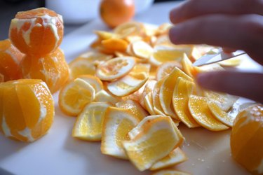 Cropped Hand Reaching For Oranges On Table