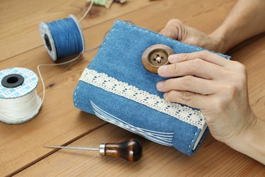 Cropped Hands Of Person Sewing Purse On Table