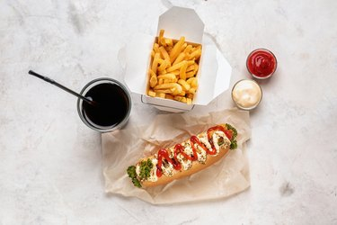 Tasty hot dog with sauces, french fries and drink on light table