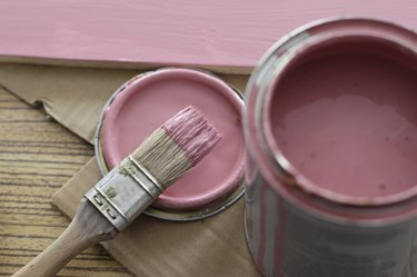 Pink paint can with brush on pink background