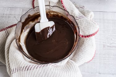 A bowl of chocolate brownie ingredients being stirred by a spatula.