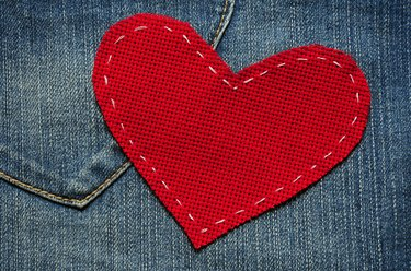Red textured heart on jeans background