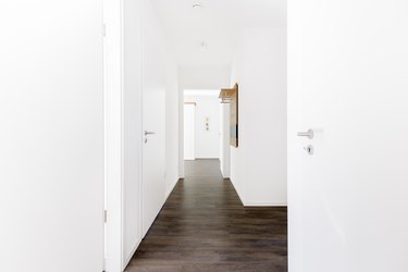 interior hallway with clean, white walls and closed doors