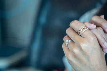 Close up of an elegant engagement diamond ring on beautiful Asian woman's finger