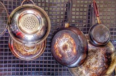 Saucepans And Kitchen Utensils Hanging On Backsplash At Home