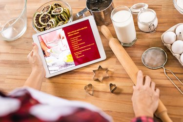 Woman holding touchpad with recipe and rolling-pin before making cookies at home