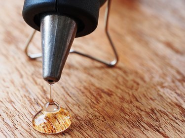 closeup hot glue gun with melted glue dripping out