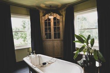 Interior view of bathroom with wooden corner cabinet  between sash windows, roll top bath with brass bath caddy.