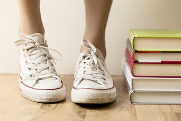 White sneakers and stack of books on the floor. Student, education and knowledge concept