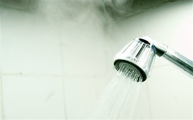 Close-Up Of Flowing Water From Shower Faucet With Steam In Bathroom