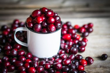 Cranberries on a mug on rustic wooden background