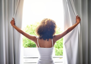Woman opening bedroom curtains, seen from behind