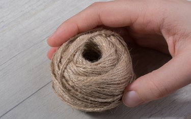 Close-Up Of Hand Holding Twine On Table