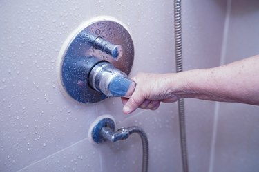 Cropped Hand Of Woman Holding Handle Of Faucet On Wall In Bathroom