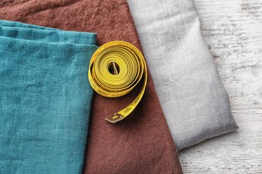 Pieces of fabric and measuring tape on wooden background