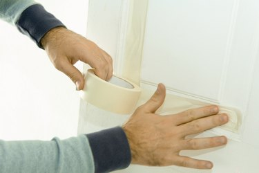 Man putting masking tape on door woodwork, close-up of hands