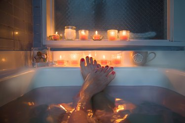 Feet in bath, candles in background