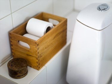 Toilet paper in crate on bathroom shelf