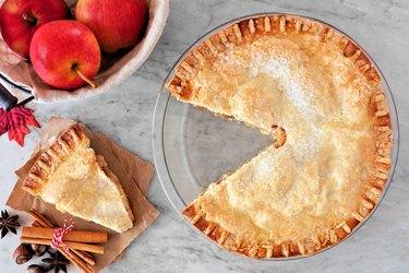 Apple pie, overhead scene with cut slice on marble background
