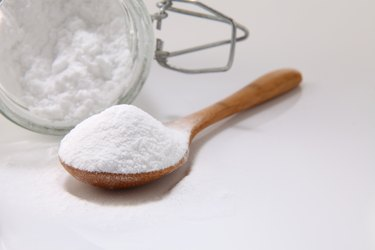Close-Up Of Baking Soda In Wooden Spoon And Jar On White Background