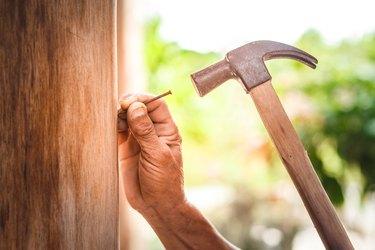 Man Hammering Nail On Wood