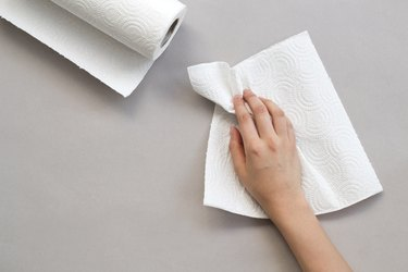 Woman wiping table with paper towel