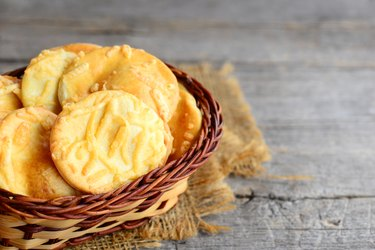 Crispy cheese cookies. Homemade baked cheese cookies in a wicker basket on a vintage wooden background. Closeup