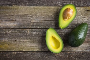 food background with fresh organic avocado on  old wooden table