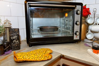 Cake pan inside a countertop oven, positioned diagonally in the corner
