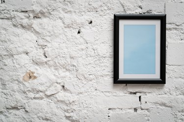 Blank frame on old white brick wall
