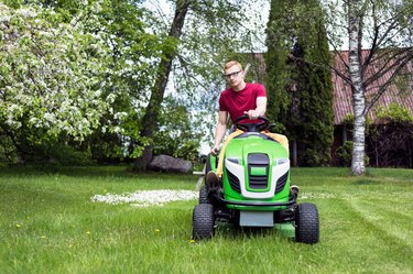 Young Man Riding Lawn Mower At Grassy Field