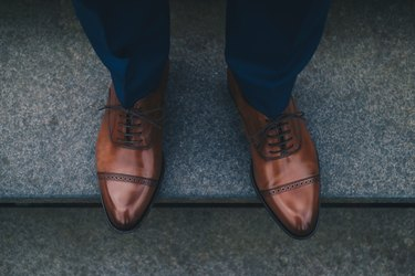 Low Section Of Man Wearing Shoes While Standing On Steps