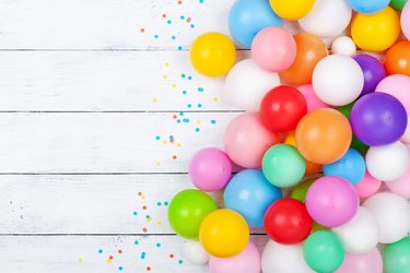 Colorful balloons and confetti on white table top view. Festive or party background. Flat lay. Birthday greeting card.