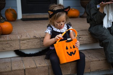 Girl in cat costume peering into trick or treating bag on porch stairway