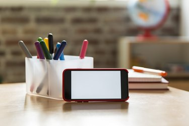 Smartphone on wooden table in children's room