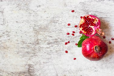Ripe juicy pomegranate fruit on white wooden rustic background