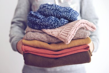 Woman holding stack of sweaters