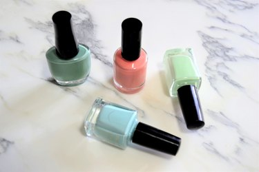 Nail polish on pastel colors on marble background
