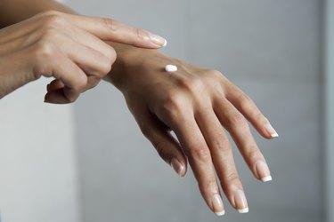 Woman moisturizing hands, cropped