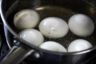 white eggs boiling in pot of hot water