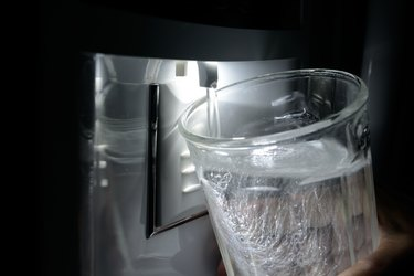 Glass being filled at refrigerator water dispenser