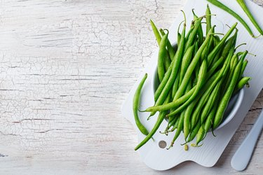 Green beans in white bowl on cutting board. Top view. Copy space