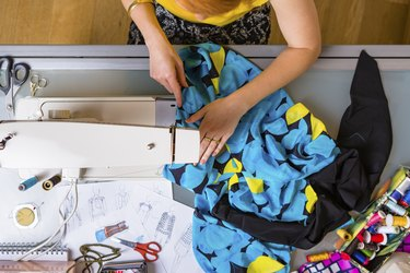 Fashion designer working with sewing machine, top view