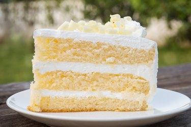 Vanilla sponge cake with cream and white chocolate decorate. Sliced piece of cake on white plate. Served on wooden table.