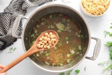 Add broth, chickpeas and bay leaf