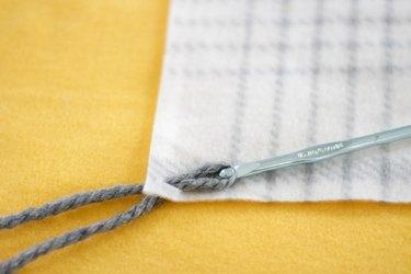 crochet hook pulling yarn through hole