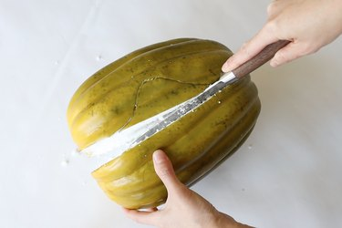 Cutting faux green pumpkin in half with knife
