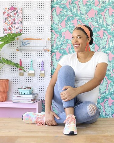 Amber posing next to craft supplies in front of a decorative wall.