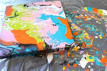 colorful canvas with paint splatters on tarp