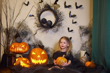 Halloween Child with pumpkin in hands in interior house. Blonde on web and bat.